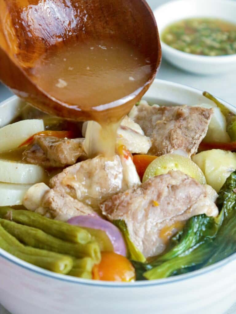 pouring broth in a bowl of sinigang na baboy