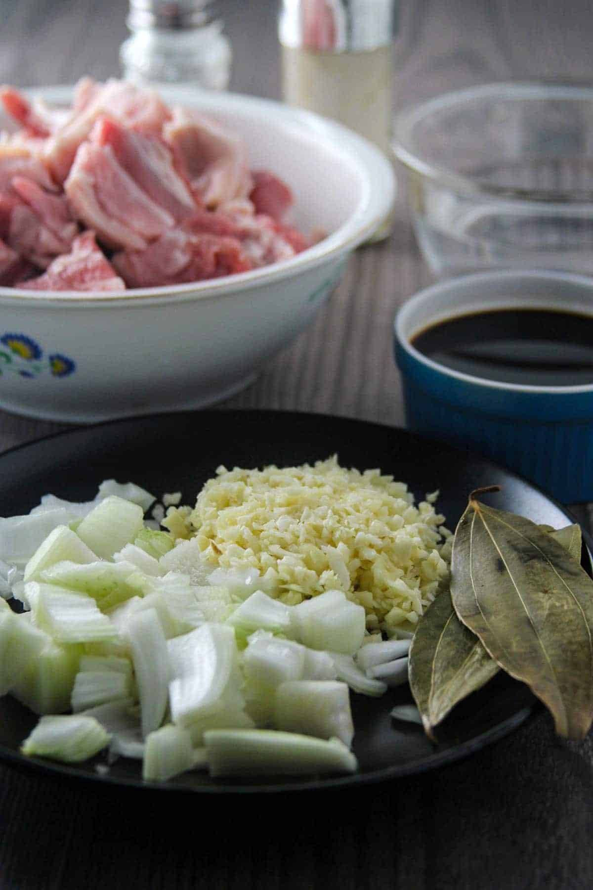 chopped onions, minced garlic, bay leaves on a black plate, soy sauce in a small blue bowl, vinegar in a clear bowl, and pork belly cubes in a white bowl
