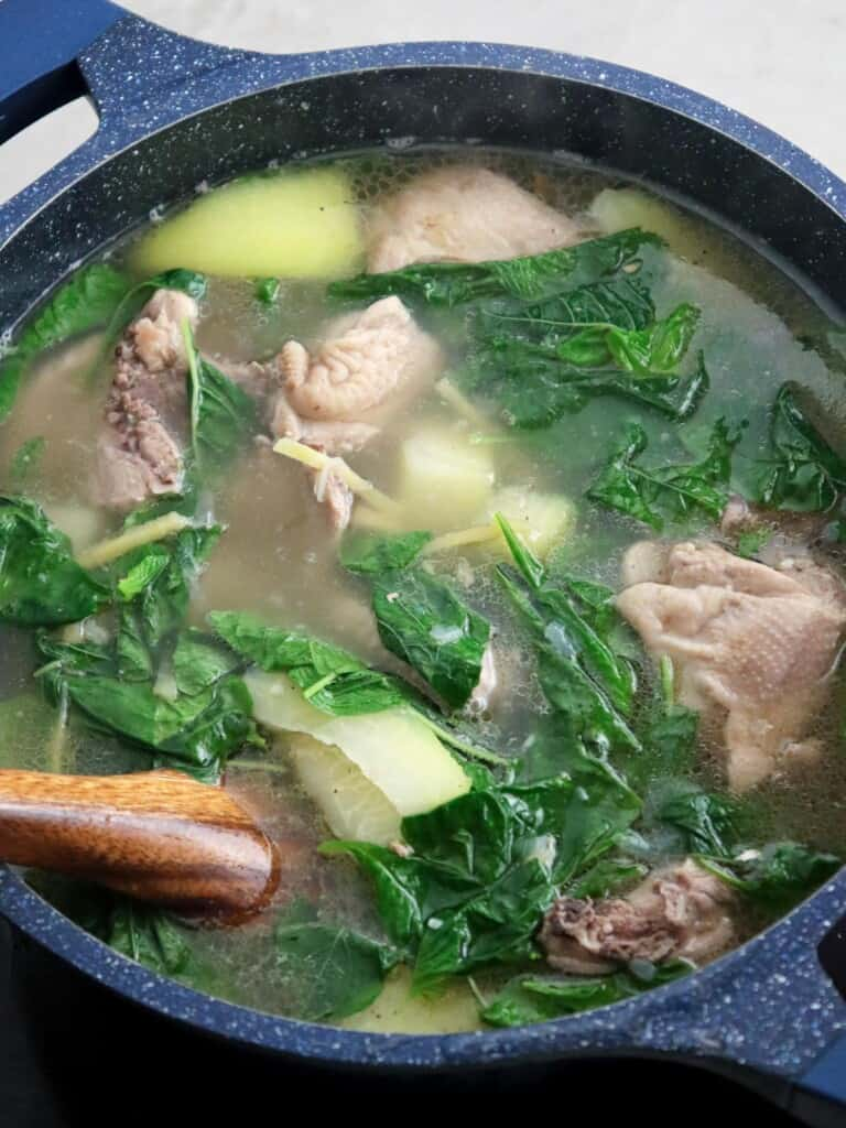 chicken tinola in a pot with spinach and green papaya