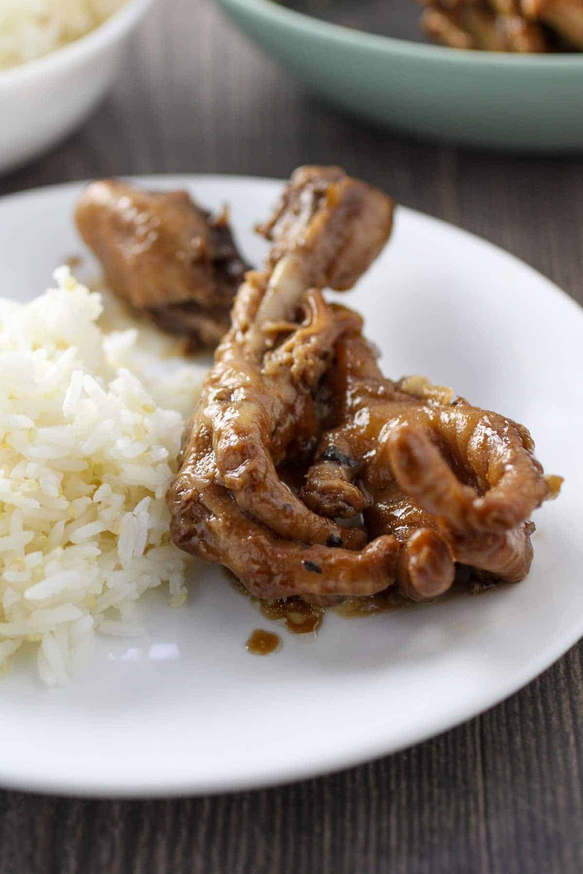 chicken feet adobo on white plate with steamed rice