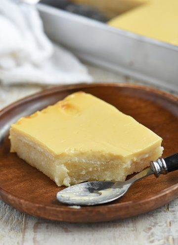 slice of cassava cake on a wooden plate with a spoon