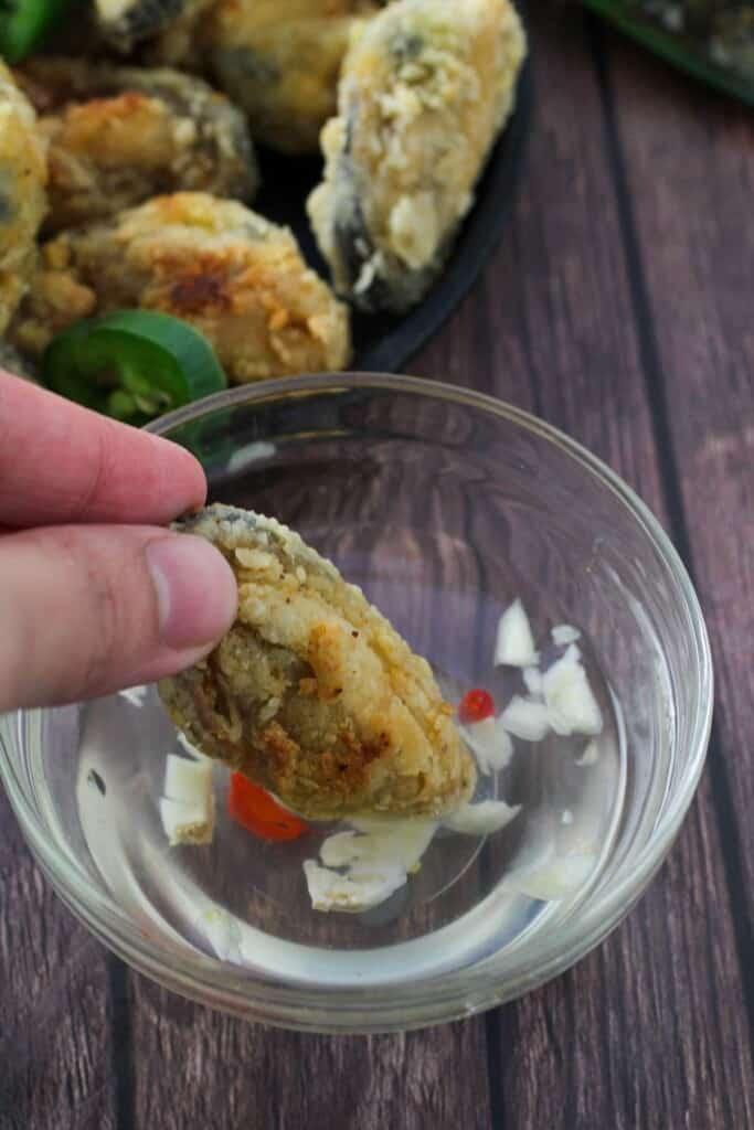 dipping crispy tahong in spicy vinegar