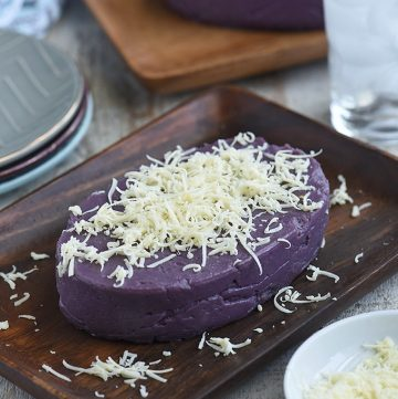 Halayang Ube topped with shredded cheese on a wooden platter