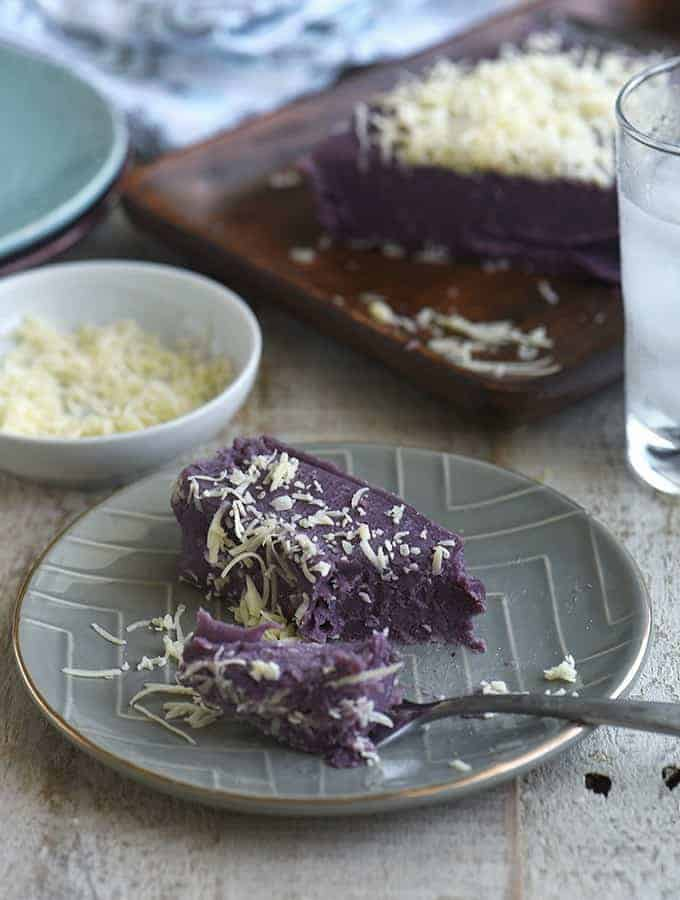 slice of ube halaya with shredded cheese topping on a gray serving plate