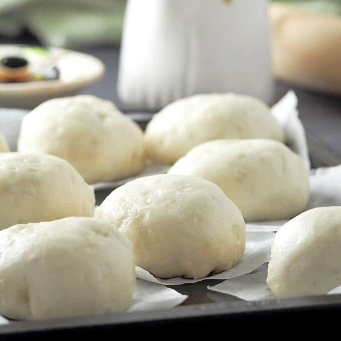siopao bola bola on a baking sheet with white jug of siopao sauce on the side
