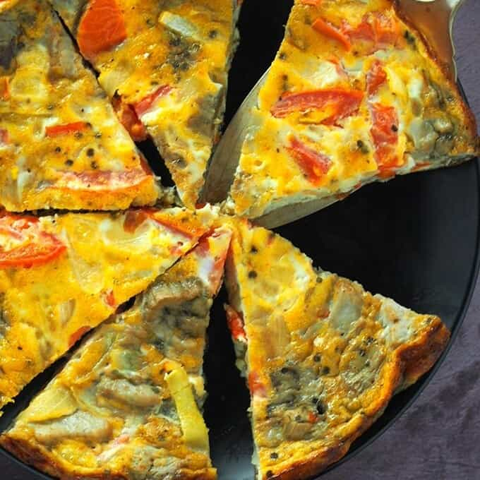 sliced roasted eggplant and tomato frittata on a black serving plate