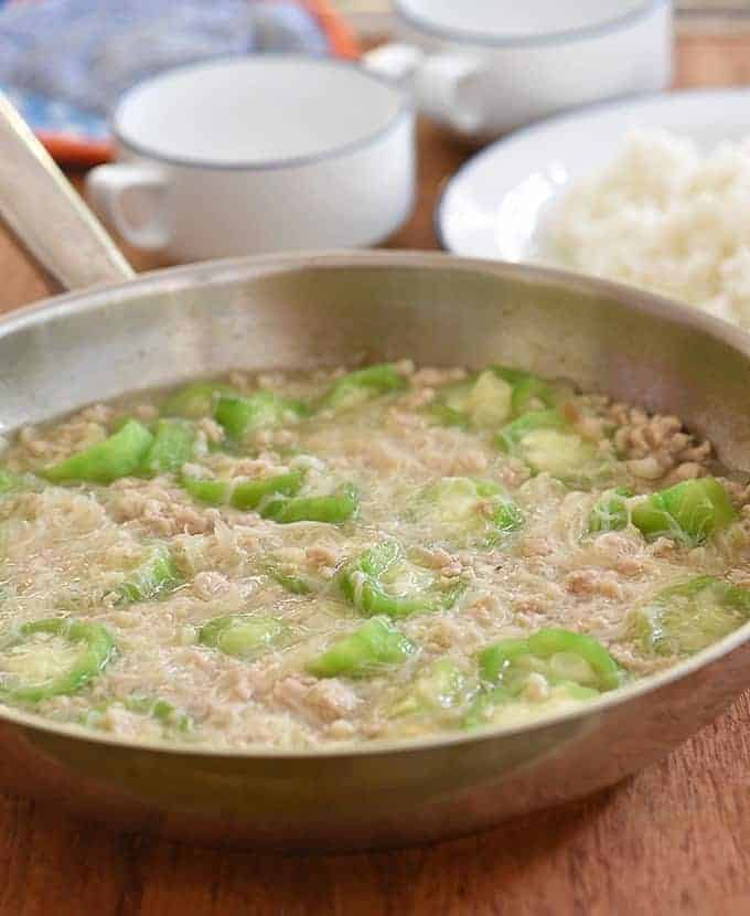 misua with patola and ground pork soup in a wide pan with a plate of rice on the side
