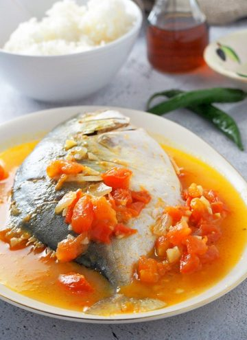 Pinangat na isda on a white serving platter with a side of steamed rice in a white bowl and fish sauce