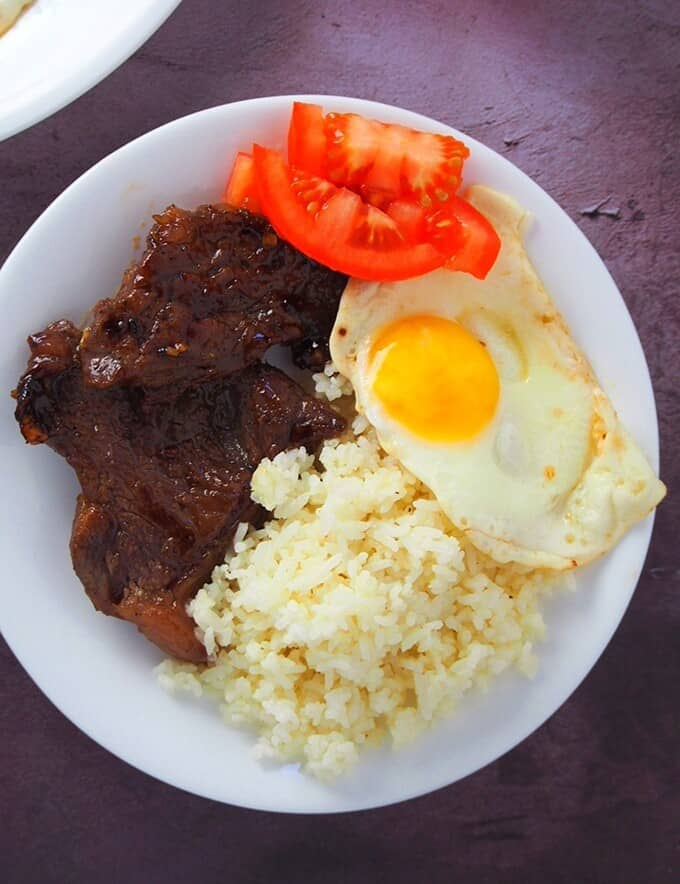 beef tapa with garlic fried rice and sunny side up eggs on a white plate