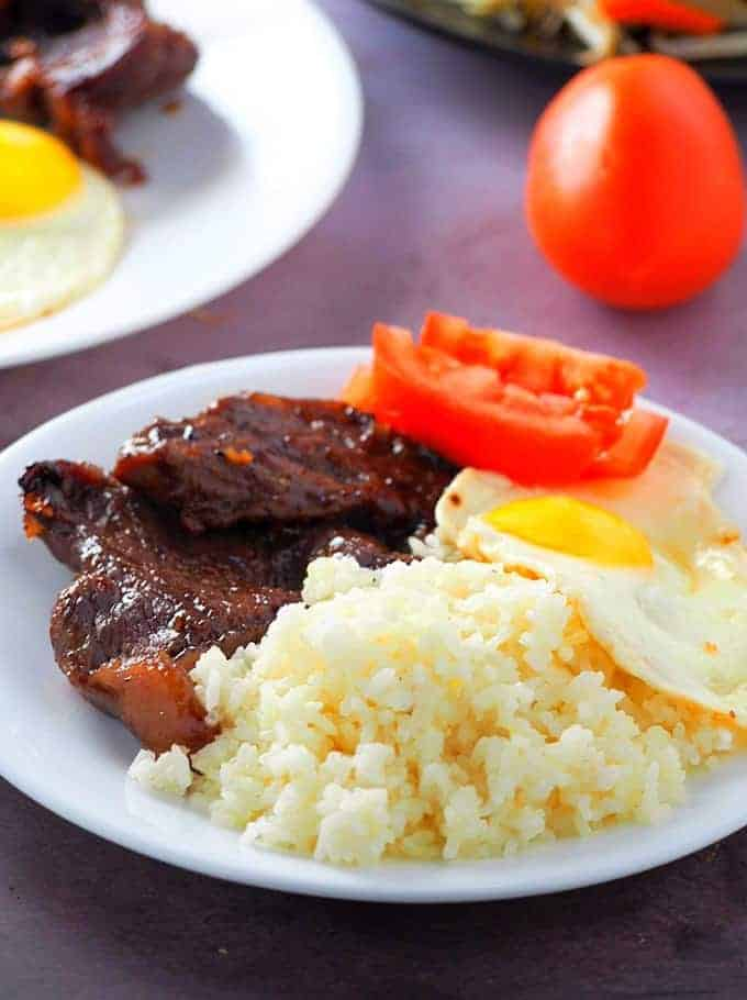 Beef Tapa with fried rice rice, fried egg, and sliced tomato on a white plate