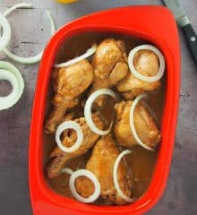 top view of Chicken Bistek with onion garnish in a red dish