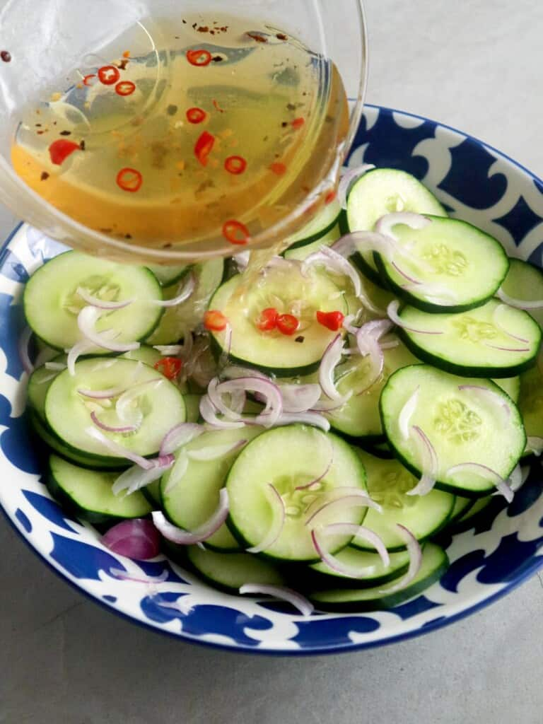 pouring vinaigrette over cucumber salad in a bowl