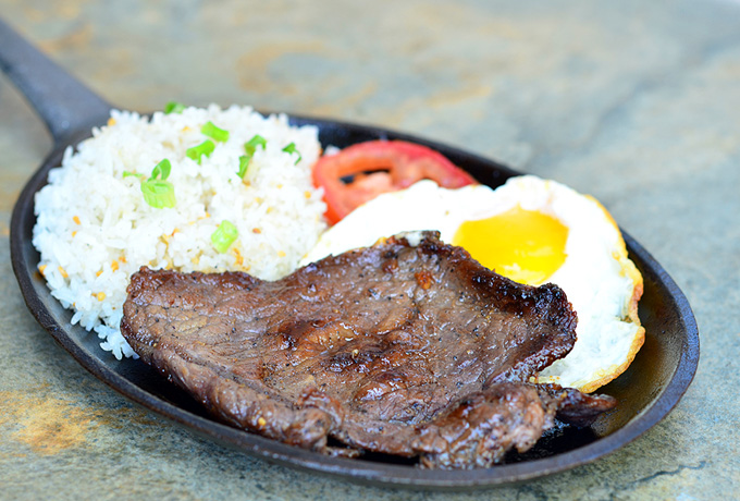 This grilled beef served with rice, a fried egg and tomatoes is seasoned and tasty.