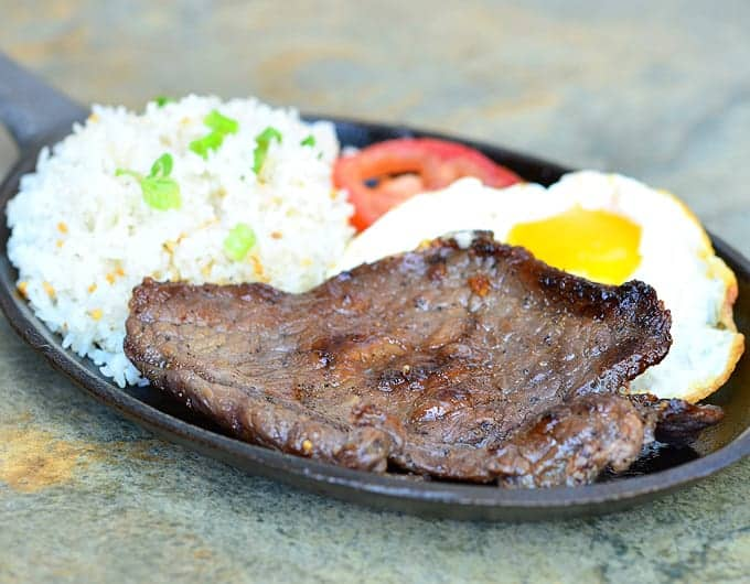 This Asian breakfast is served with rice, a fried egg and tender steak.