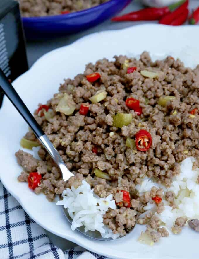 bagis with chopped red chili peppers over rice on a white serving plate