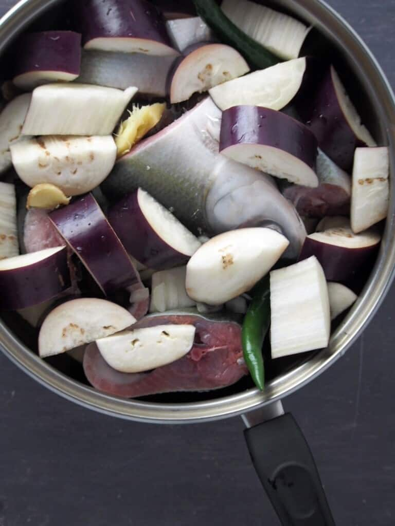milkfish, eggplant, ginger, garlic, onions, vinegar, and chili peppers in a wide pan