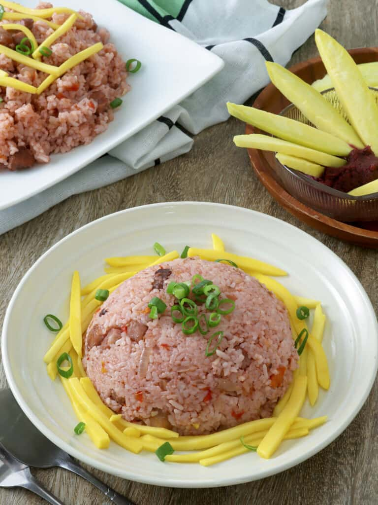 Binagoongan fried rice with sliced mangoes on a serving plate