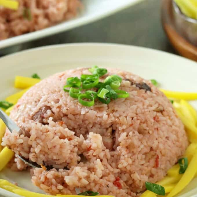 eating binagoongan rice with a fork on serving plate