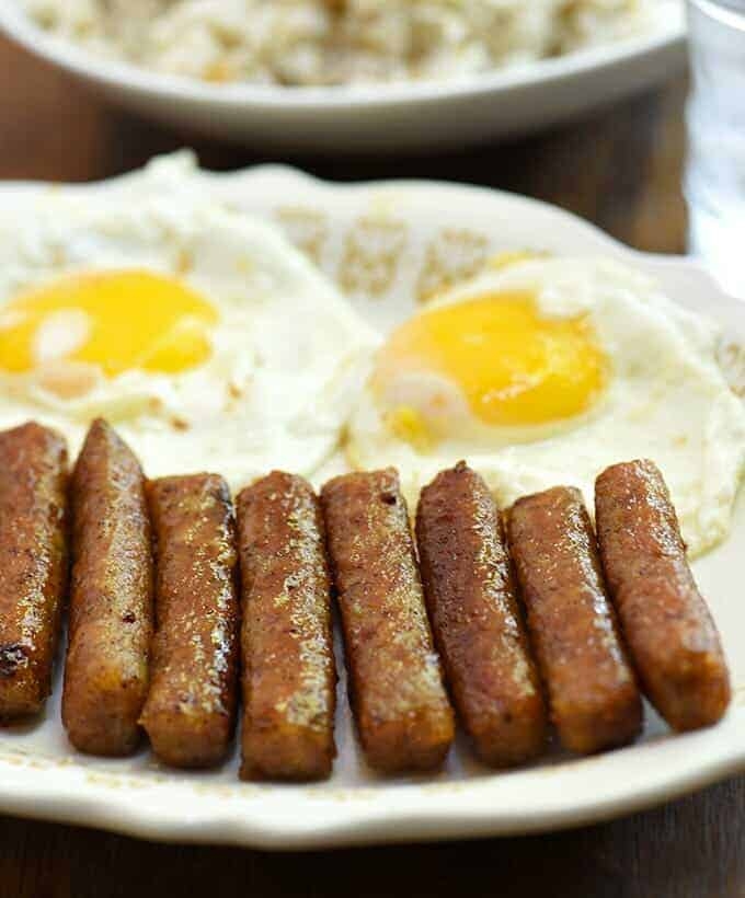 skinless longganisa and fried eggs on a white serving platter
