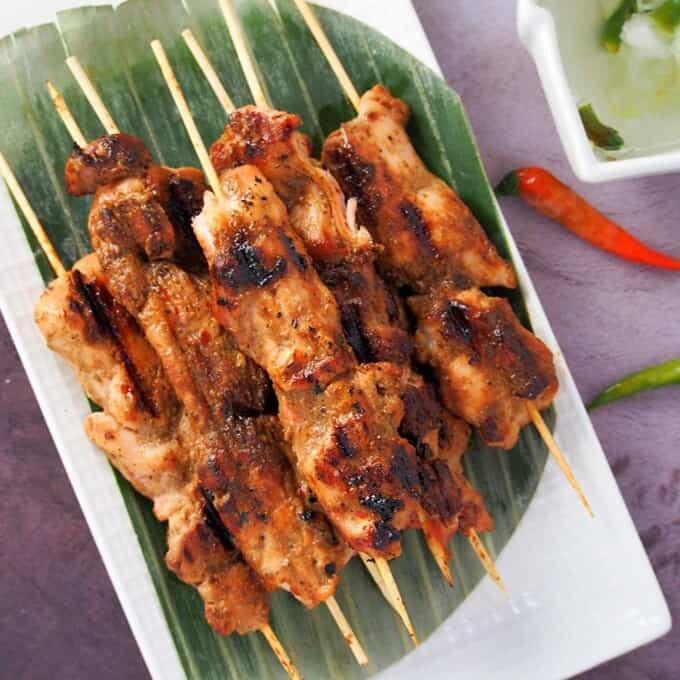 Filipino-style chicken bbq sticks on a white platter