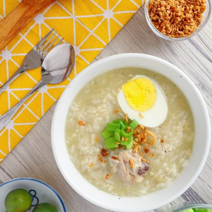 Chicken Arroz Caldo in white serving bowls topped with boiled egg, green onions, and fried garlic bits