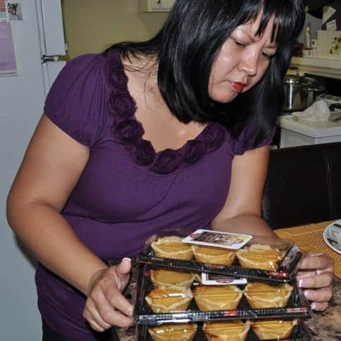 woman packing mini egg pies in plastic containers