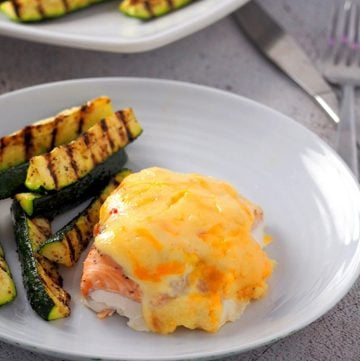 Baked Salmon with Sweet Chili-Mayo Topping on a white plate with grilled zucchini