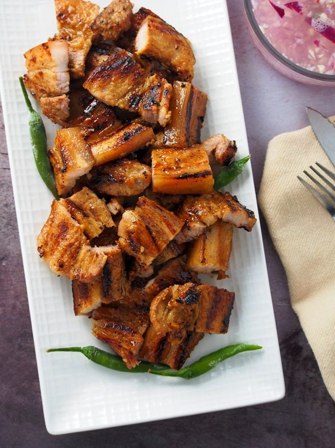 top view of Filipino-style grilled pork belly on a white serving platter