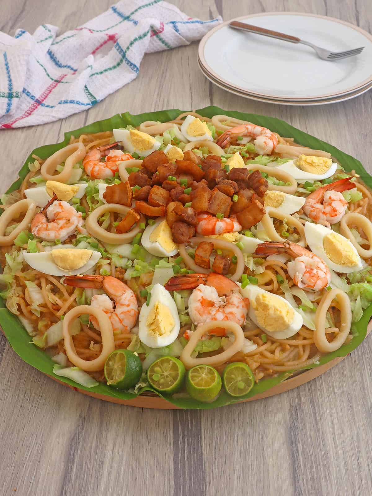 Pancit Malabon with assorted toppings on a bilao