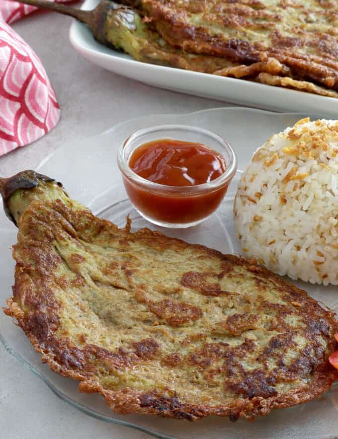 eggplant omelette on a plate with steamed rice and ketchup