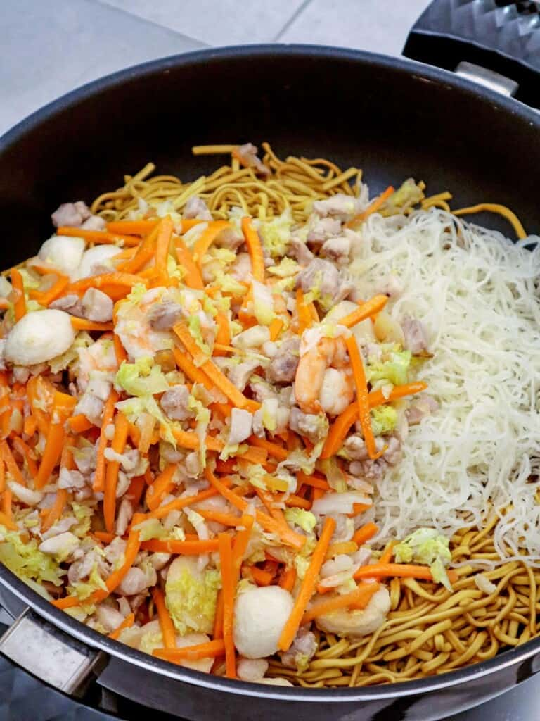making miki bihon in a pan with chicken, shrimp, fish balls and veggies