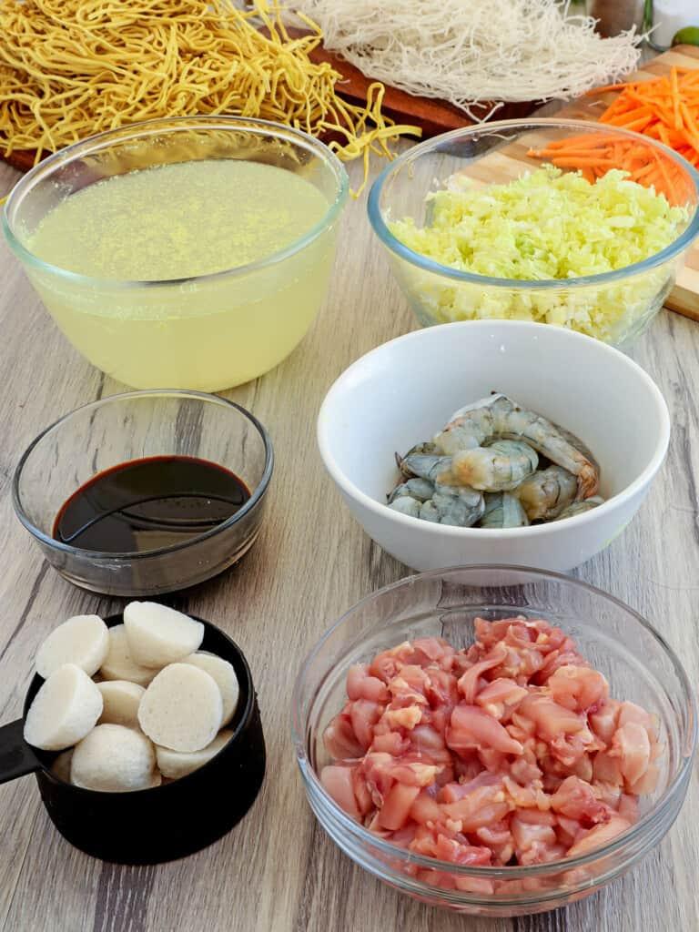 fresh egg noodles, rice stick noodles, sliced chicken, fish balls, peeled shrimp, chicken broth, shredded cabbage, julienned carrots, kecap manis in individual bowls