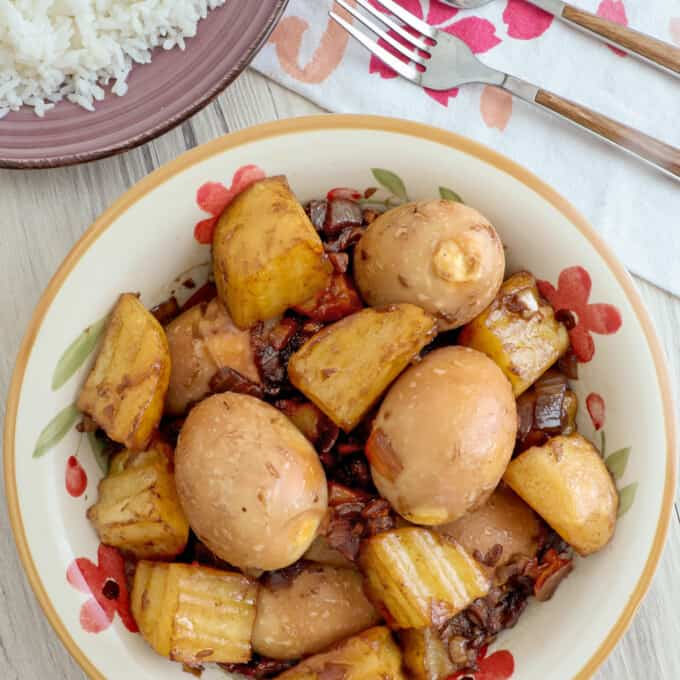 Adobong Itlog in a white serving bowl with a plate of steamed rice on the side