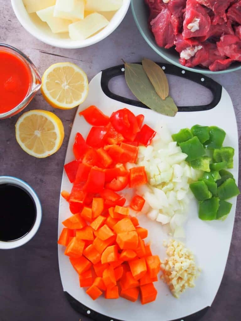 chopped onions, garlic, bay leaves, cubed bell peppers, sliced lemon, tomato sauce, soy sauce, cubed potatoes, carrots and beef