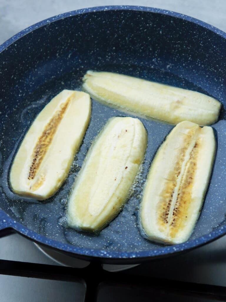 frying sliced saba bananas in a pan