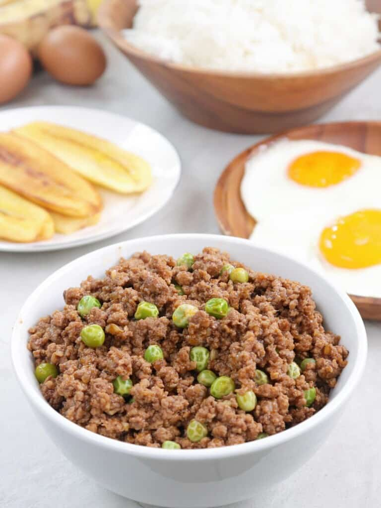 Arroz a la Cubana in a white serving bowl with fried saba, fried eggs, and steamed rice on the size
