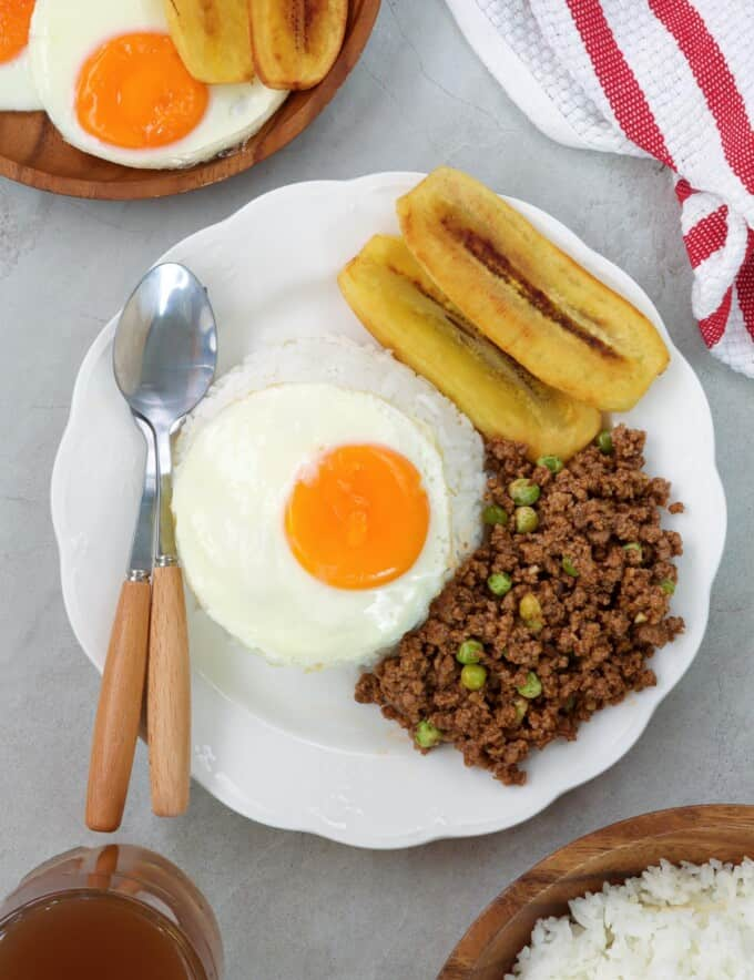 cuban rice with ground beef hash, fried egg, fried bananas, and white rice on white serving plate