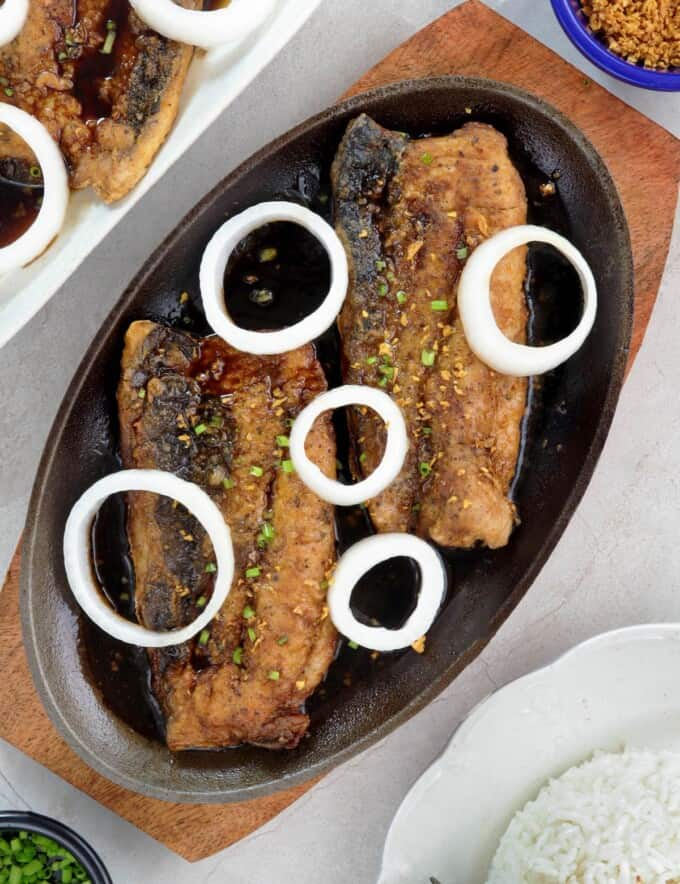 bangus a la pobre with onions and crispy garlic on a sizzling plate
