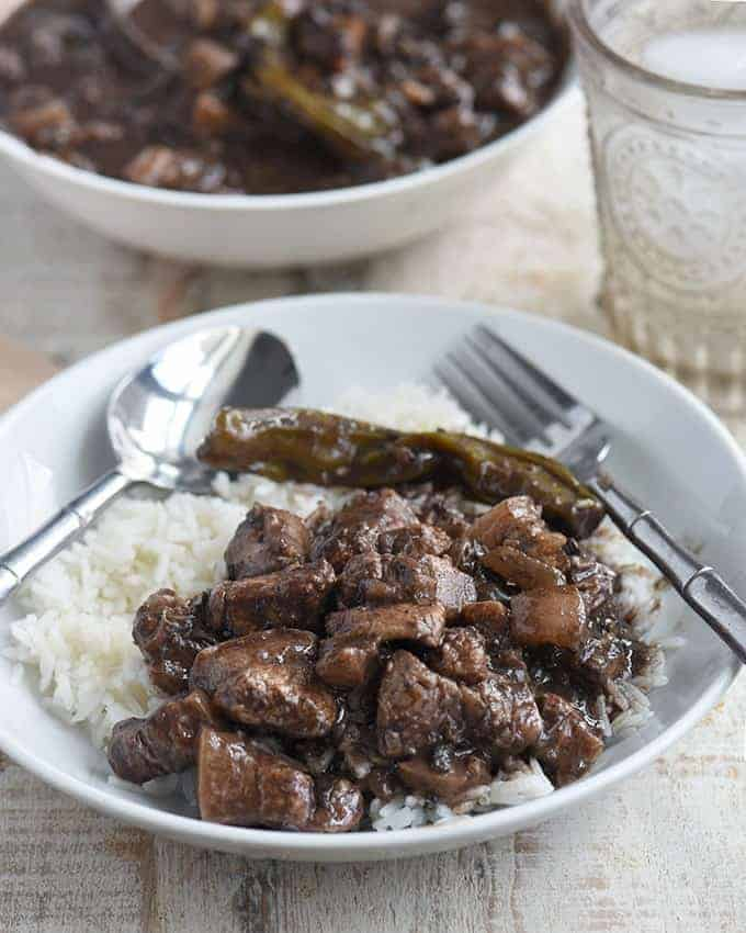 dinuguan over steamed rice on a white serving plate