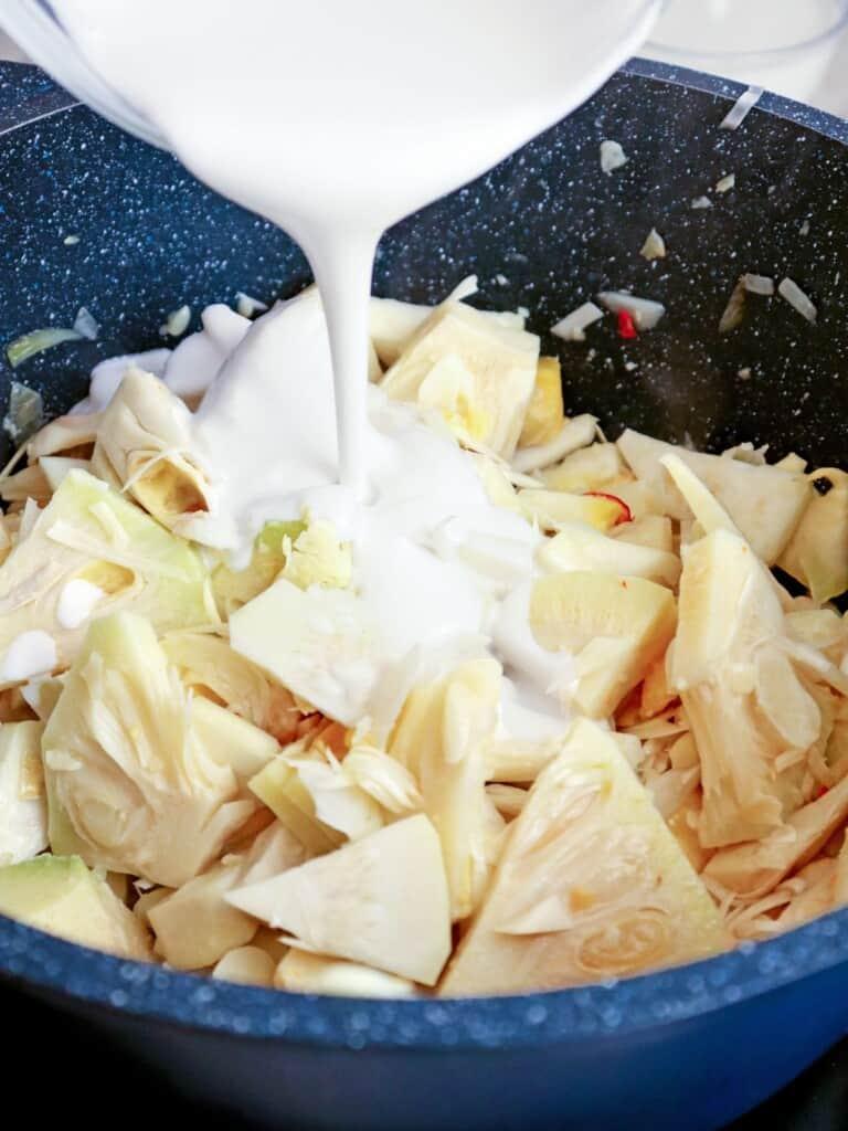 adding coconut milk to a pan of sliced jackfruit