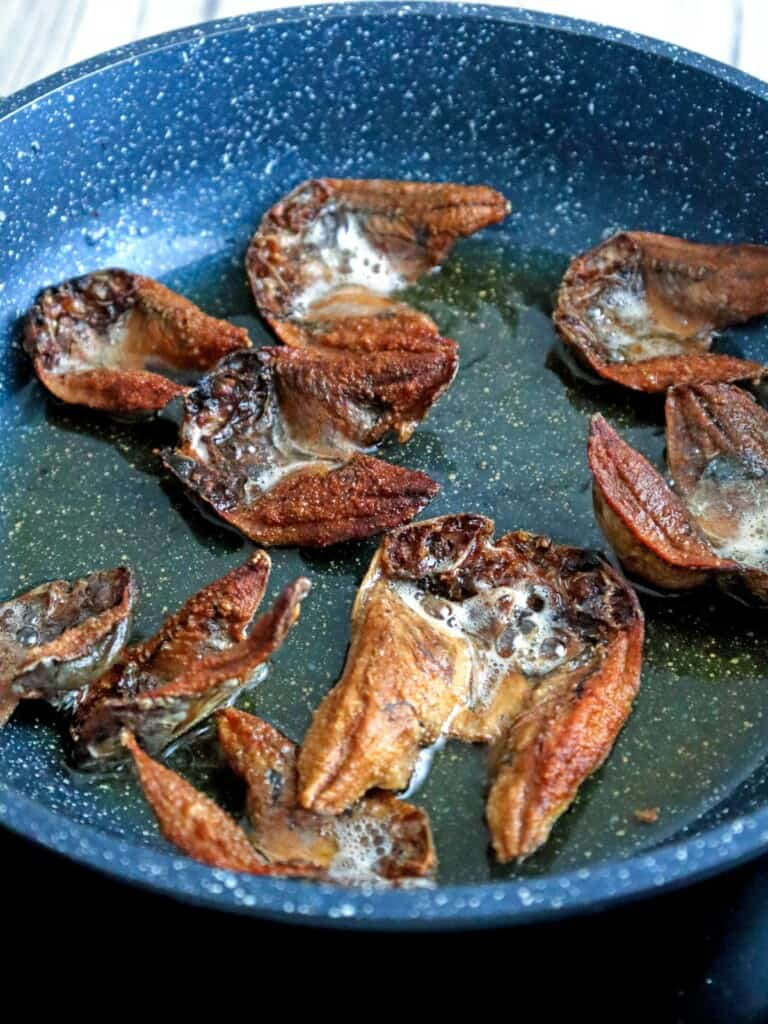 frying dried fish in a pan