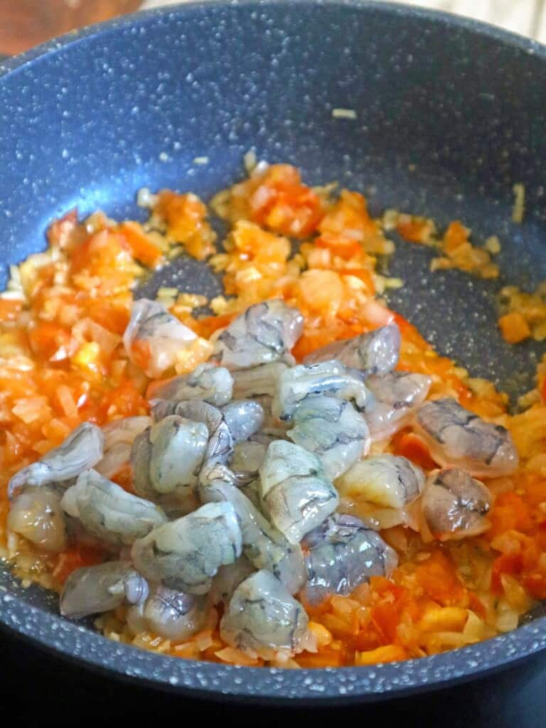sauteing shrimp in onions, garlic, and tomatoes in a pan