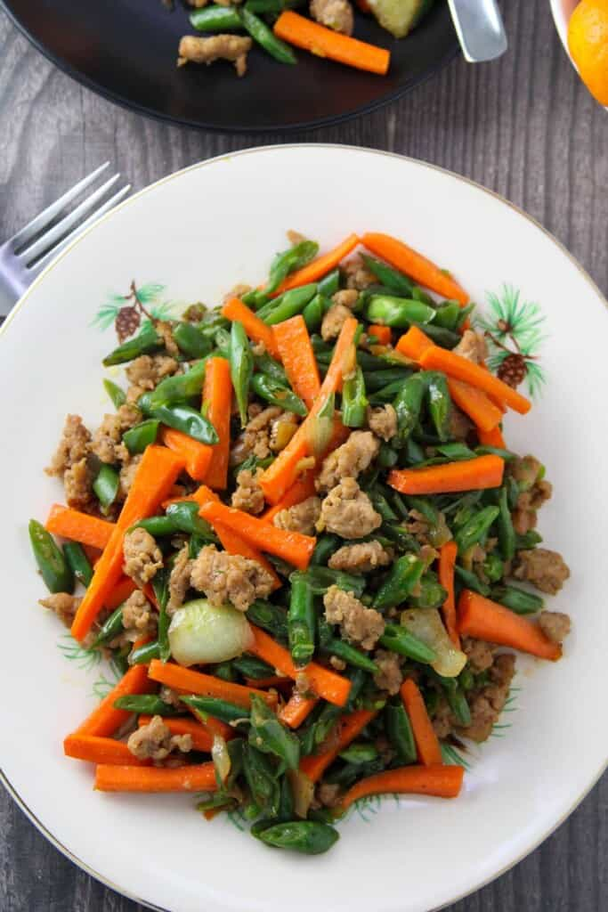 green bean stir-fry with carrots and minced pork on a white serving platter