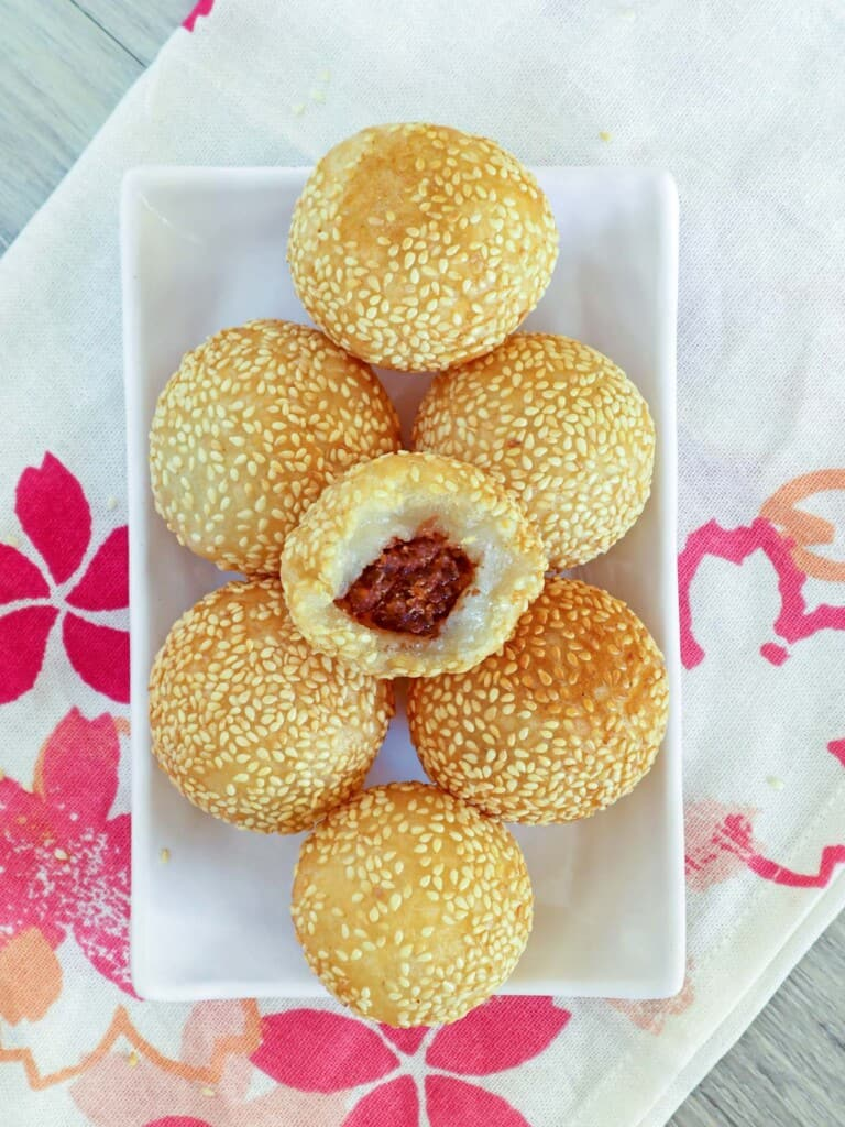 sesame balls with red bean filling on a white plate