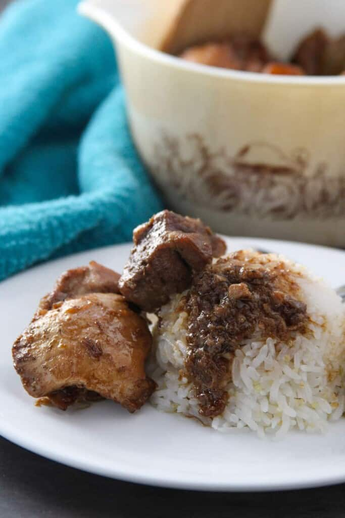 adobong manok at baboy over steamed rice on a white plate