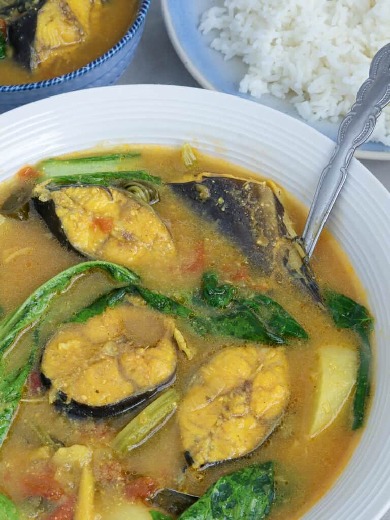 catfish sinigang with miso and mustard leaves in a white serving bowl