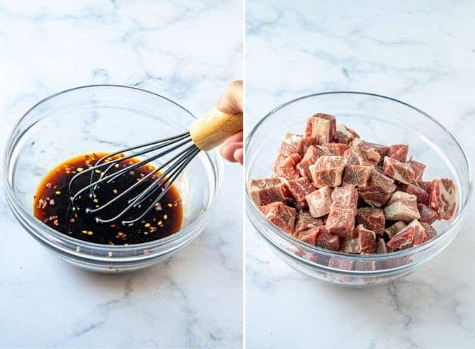 cubed ribeye steaks in a glass bowl and soy sauce marinade mixture in another glass bowl
