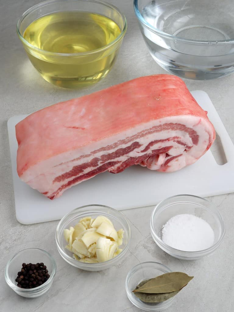 raw pork belly, oil, garlic, salt, peppercorns, bay leaves