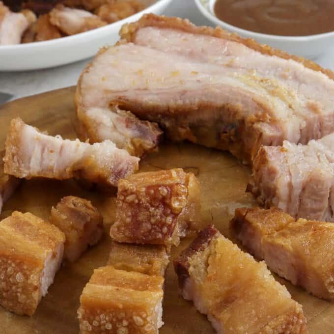 crispy pork belly on a wooden chopping board