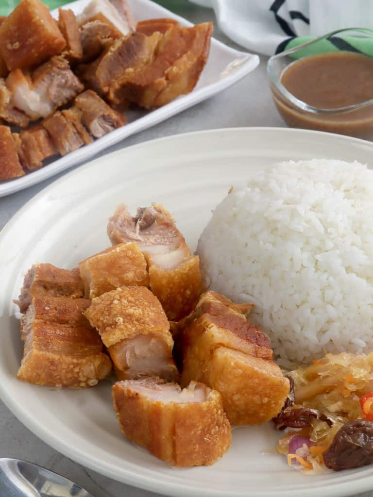 chopped lechon kawali with steamed rice on a white plate